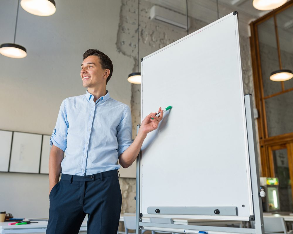 attractive young handsome smiling man standing at empty white board with marker, leadership business training in open space office, successful modern youth, online education